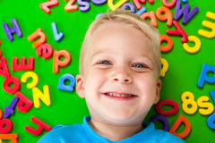 Preschool child with letters. A cute 3 year old boy laying on a mat covered with letters and numbers Stock Images