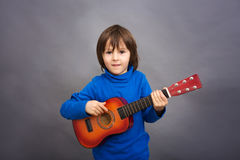Preschool child, playing little guitar, image. Studio shot Royalty Free Stock Photos