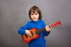Preschool child, playing little guitar, isolated image. Studio shot Stock Photos