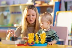Preschool child, playing with toys in a sunny room, kid development. Preschool child, playing with toys in a sunny room. Nursery teacher helps baby. Kidd stock images