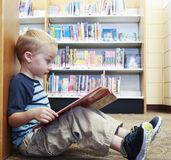 Preschool child reading a book at the library Stock Image