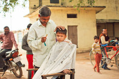 Preschool child with unhappy face doing new hairstyle by village barber Royalty Free Stock Image