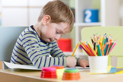 Preschool child use pencils and paints for homework received from kindergarten Stock Images