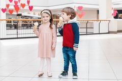 Preschool children boy and girl eating licking ice-cream. Group portrait of two white Caucasian cute adorable funny preschool children boy and girl eating stock photos