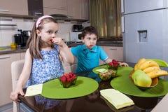 Preschool children eat strawberry in the kitchen Royalty Free Stock Image