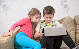 Preschool children having fun with pad while sitting on sofa in domestic room Royalty Free Stock Image