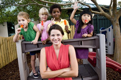 Preschool children on playground with teacher. Diverse group of preschool 5 year old children playing in daycare with teacher stock photo