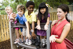Preschool children on playground with teacher. Diverse group of preschool 5 year old children playing in daycare with teacher royalty free stock photo