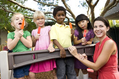 Preschool children on playground with teacher. Group of preschool 5 year old girls eating popsicles in daycare with teacher royalty free stock images