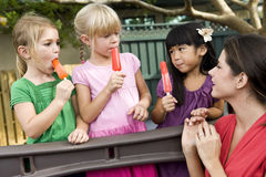 Preschool children on playground with teacher. Group of preschool 5 year old girls eating popsicles in daycare with teacher stock photo