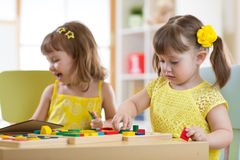 Preschool children playing with educational sorter toys in classroom, kindergarten or home. Preschool kids playing with educational sorter toys in classroom royalty free stock photo