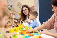 Preschool children sticking with plasticine in classroom. Preschool kids sticking with plasticine in classroom in kindergarten stock photos