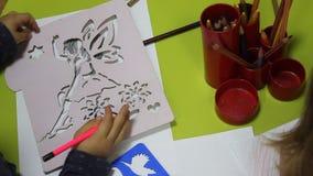 Preschool children using crayons stock footage