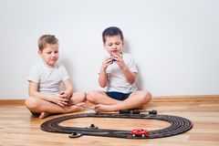 Preschool children in white t-shirts playing with a toy track and cars. Indoors royalty free stock photography