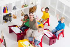 Preschool class. Overhead of a happy preschool class and teacher waving and looking up in classroom stock image