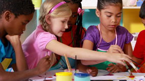Preschool class painting at table in classroom. In playschool stock video footage