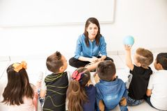 Preschool class sitting on the floor. Attractive young women teaching her preschool students while they all sit on the classroom floor stock photos