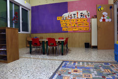 Preschool classroom with red chairs and table. With drawings of children hanging on the walls stock photography