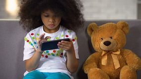 Preschool curly african girl studying letters on smartphone, educational apps