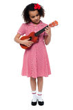 Preschool cute girl playing a guitar Royalty Free Stock Images