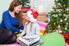 Preschool daughter with mother sitting on floor next to Christmas tree Royalty Free Stock Images