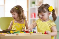 Preschool dzieci bawić się z edukacyjną brakarką bawją się w sala lekcyjnej, dziecinu lub domu, zdjęcie royalty free