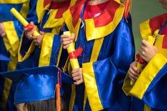 Preschool dzieciak jest ubranym skalowanie suknię i trzyma dyplomu zbliżenie obrazy stock
