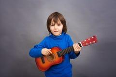 Preschool dziecko, bawić się małą gitarę, wizerunek zdjęcia royalty free