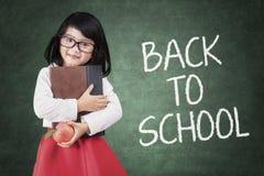 Preschool dziewczyna z jabłkiem i książką Obraz Royalty Free