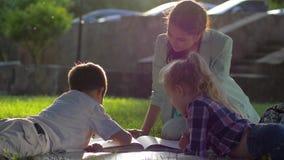 Preschool edukacja, piękna kobieta czyta książkę dla chłopiec i dziewczyny obsiadania na zielonej trawie outdoors w pogodnym świe zbiory