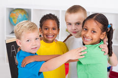Preschool friends. Four happy diverse preschool friends hugging in a circle in classroom Stock Photos