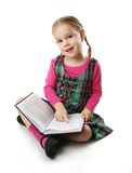 Preschool girl. Cute preschool age girl sitting down reading a book Royalty Free Stock Images