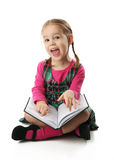 Preschool Girl. Cute preschool age girl sitting down reading a book with a surprised happy face Royalty Free Stock Images