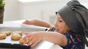 Preschool girl baker holding a baking sheet with cookies. Close up Royalty Free Stock Image