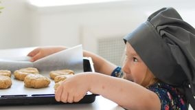 Preschool girl baker holding a baking sheet with cookies. Close up Stock Photos