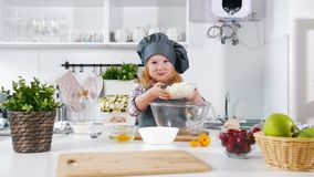 Preschool girl baker on kitchen mixes and tastes the dough in a bowl. Close up stock video