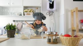 Preschool girl baker kneads the dough with a large wooden spoon in a bowl. Close up stock video footage