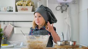 Preschool girl baker mixes the dough in a bowl. Close up stock video