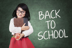 Preschool girl with a book and apple Royalty Free Stock Image