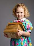 Preschool girl carrying books Stock Photography