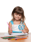 Preschool girl at the desk. A preschool girl sits at the desk and draws royalty free stock photography