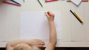 A preschool girl draws with colored pencils. View from above. A preschool girl draws with colored pencils. View from above stock video