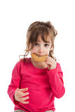 Preschool girl eating cookie. Portrait of adorable 3 year old girl eating a chocolate chip cookie isolated on white background Stock Photos