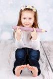 Preschool girl holding big crayon Stock Photos