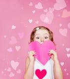 Preschool girl holding paper heart. Cute preschool girl holding pink paper heart in hands Royalty Free Stock Image