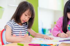 Preschool girl kid drawing with color pencil on white paper on t. Able in classroom with friends and teacher,Kindergarten education concept royalty free stock photos