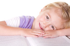 Preschool girl laying on large book Stock Photography