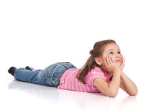 Preschool girl lying on floor. Girl lying on floor and watching something. Isolated background, reflection foreground Royalty Free Stock Images