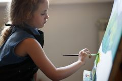 Preschool girl painting in art class. Close up photo brush in hand.  royalty free stock image