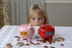 Preschool girl and piggy banks Royalty Free Stock Photography
